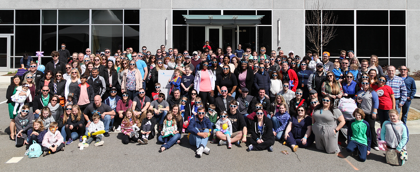 Large group of adults and children posing and wearing sunglasses.